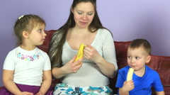 Pregnant woman with young children eating bananas. Happy family waiting for - stock footage