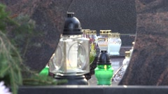 Green and white votive candle lit on black marble tombstone. Stock Footage