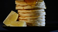 Shrove Tuesday breakfast with honey pouring over tall stack of pancakes with lem Stock Footage