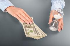 Woman touches hourglass and cash. Stock Photos