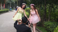 Chinese young women in the park to take a picture of Art Stock Footage