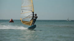 Young Man Windsurfing in Sea. Open Windsurfing Competitions - stock footage