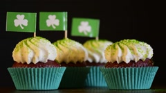 Female hand decorating St Patricks Day cupcakes with Shamrock Flags. Stock Footage