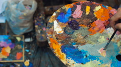 Artist mixes oil paints on pallet with various colors - stock footage