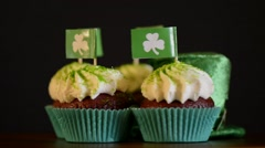 Rotating St Patricks Day cupcakes with small lechrechaun hat against a black  Stock Footage
