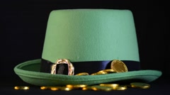 St Patricks Day gold coins falling on green leprechaun hat. - stock footage