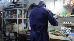 Worker working in his shop, wearing blue suit, panning left to right Stock Footage