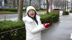 Asian girl enjoying snow in a snowy day in the street of a town.. Stock Footage