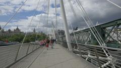 Parents with children walking on Golden Jubilee Bridges in London Stock Footage
