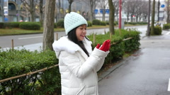 Asian girl enjoying snow in a snowy day in the street of a town Stock Footage
