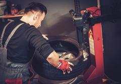 Professional car  mechanic replace tire on wheel in auto repair service. - stock photo