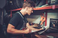 Professional car mechanic at his workplace preparing checklist in auto repair Stock Photos