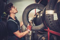 Professional car  mechanic choosing new tire in auto repair service. - stock photo