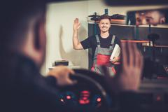 Professional car mechanic welcomes new client to his auto repair service. - stock photo