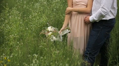 Loving couple standing in the grass.girl with a bouquet of flowers - stock footage