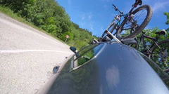 Car with bikes on bicycle roof rack driving on a winding  road in the summer Stock Footage