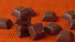 Chocolate candies over orange background Stock Footage