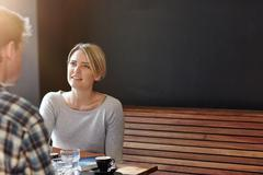 Stock Photo of Young woman having coffee with man against dark grey background