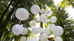 Beautiful decor  for a party of white paper Chinese lanterns hanging in a tree. Stock Footage