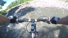 Point of view man riding bike crossing mountain creek with a destroyed bridge Stock Footage