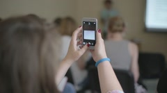 Girl makes a photo on smartphone during the conference Stock Footage
