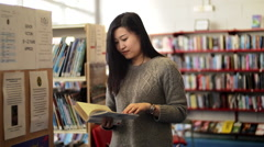 An Asian good friend reading a book at the library Stock Footage