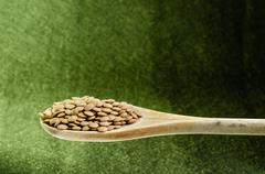 Lentils in a spoon, close up, color background. Stock Photos