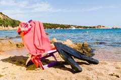 deckchair with diving mask and flipper, on the beach, sunny day.. - stock photo