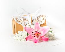 Fresh pink lily flower and gift box as a present for a holiday. Stock Photos
