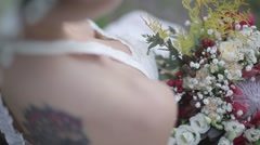 Bride with a tattoo on her back and holding flowers - stock footage