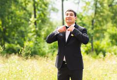 portrait of handsome stylish groom in black classic suit outdoors - stock photo