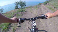 Mountain biker point of view man cyclist riding a bicycle down side of hill Stock Footage
