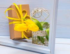 Gift box with a ribbon and yellow tulips in decorative cage Stock Photos