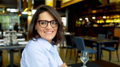 Businesswoman sitting in the restaurant and smiling to the camera, steadycam sho Stock Footage