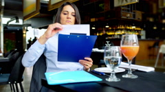 Businesswoman working on papers and doing serious look, steadycam shot Stock Footage