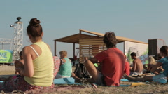 Young People Are Making Yoga Asana Sitting on the Mat on the Beach in a Bright Stock Footage