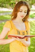 Long-haired girl reads book - stock photo