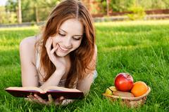 Girl with book and apples Stock Photos