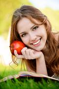 Girl with book and apple - stock photo