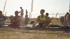 Young People Are Making Yoga Asana Sitting on the Mat on the Beach in a Bright - stock footage