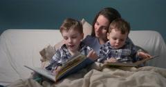 Bedtime story elder boy reading up loud  - stock footage