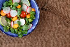 Bowl of fresh vegetable salad on jute table cloth Stock Photos