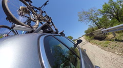 Car with mountain bikes on bicycle roof rack driving on winding coastal road Stock Footage