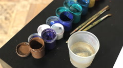 Oil paints and paint brushes on a palette Stock Footage