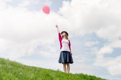 Happy girl holding air balloon - stock photo