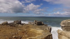 Rocky cliff by the sea with Island in the distance, steady cam - stock footage
