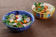 Bowls of fresh vegetable salad on jute table cloth Stock Photos