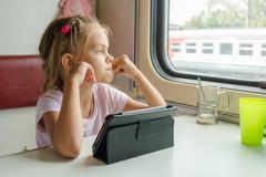 Girl thoughtfully looked out the window while sitting with a tablet on a trai Stock Photos