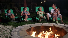 Family with friends relaxing on grassy lawn in backyard of home near fire pit Stock Footage