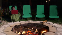 Young girl wrapped rug sitting on lounger in backyard with laptop near fire pit Stock Footage